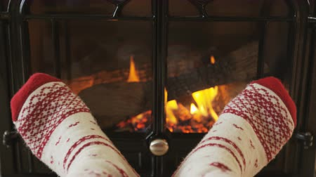 sock : Feet in socks warming by fire in fireplace. Girl is wearing socks nearby fireplace. Female is relaxing at home during winter. SLOW MOTION.