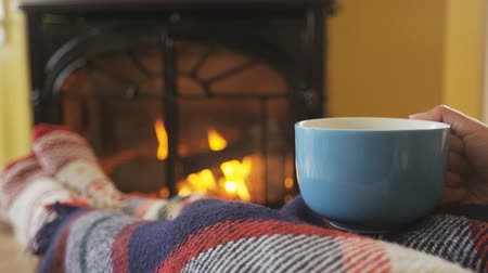 Домашняя жизнь : Woman holding coffee cup nearby fireplace in living room. Female is covering herself with blanket while drinking hot drink refreshment. She is warming herself during winter at home. Стоковые видеозаписи