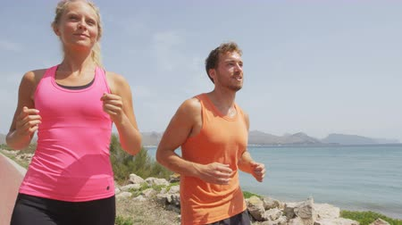 running man : Running people workout. Slow motion video of young couple jogging by ocean. Man and woman are in sports clothing. They are representing their healthy lifestyle. Stock Footage