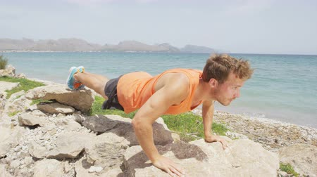 fit : Workout Push ups. Slow motion video of young man doing push ups on rocks. Handsome male is exercising on lakeshore. Determined man is in sports clothing. He is representing healthy lifestyle.