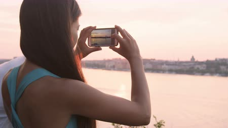 фотографий : Tourist taking photograph of sunset in Stockholm skyline and Gamla Stan. Woman photographer taking photos using smartphone. Female traveler sightseeing visiting landmarks in Sweden, Scandinavia.
