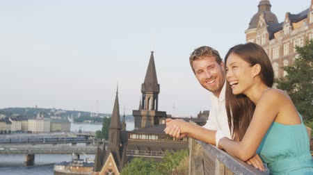 медовый месяц : Romantic couple looking at sunset view embracing. Serene man and woman in love enjoying beautiful view of Stockholm, Sweden. Young lovers on honeymoon or dating in Scandinavia.