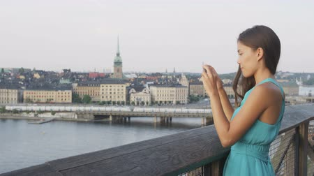 vyhlídkové : Tourist taking photo using smart phone in Stockholm skyline and Gamla Stan. Woman photographer taking photos using smartphone. Female traveler sightseeing visiting landmarks in Sweden, Scandinavia.