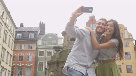 Швеция : Young couple taking self portrait selfie photo on Europe travel. Happy candid tourists on Stortorget, big square, Gamla Stan, the old town of Stockholm, Sweden. Asian woman, Caucasian man.