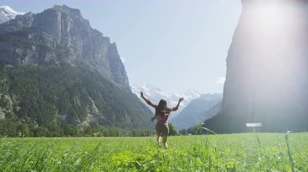 zadní : Carefree young woman running on grassy field. Rear view of female with arms outstretched enjoying in nature. Idyllic view of rocky mountains on sunny day. Swiss Alps, Switzerland.