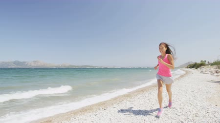 шорты : Young woman runner running on sea shore. Determined female is in sportswear. Jogging girl is exercising on sunny day. Idyllic view of beach against blue sky. Athlete living healthy lifestyle