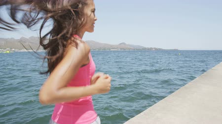 bok : Fit running young woman jogging on footpath by sea. Side view of determined female in sportswear. Smiling runner is exercising against blue sky on sunny day. She is showing her healthy lifestyle. Dostupné videozáznamy
