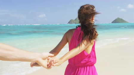 медовый месяц : Couple on beach running having fun on honeymoon on Hawaii. Romantic couple joyful and full of happiness on travel vacation on Lanikai beach, Oahu, Hawaii, USA. Asian woman, Caucasian man