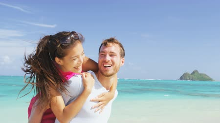 sırt : Happy beach couple in love on summer vacations on Lanikai beach, Oahu, Hawaii, USA with Mokulua Islands. Joyful Asian girl piggybacking on young Caucasian boyfriend and having fun on travel holiday. Stok Video