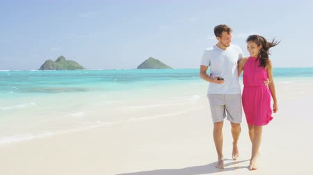 медовый месяц : Couple walking on beach vacation using smart phone app. Romantic couple in love on honeymoon having fun on Lanikai beach, Oahu, Hawaii. Couple holding smartphone