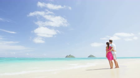 tökéletes : Beach honeymoon couple holding hands walking on white sand beach. Newlyweds happy in love relaxing on summer holidays on Lanikai beach, Oahu, Hawaii, USA with Mokulua Islands. Travel vacation concept.