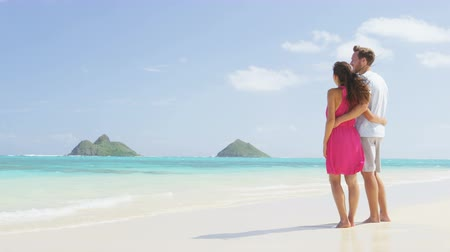 медовый месяц : Beach honeymoon couple holding hands walking on white sand beach. Newlyweds happy in love relaxing on summer holidays on Lanikai beach, Oahu, Hawaii, USA with Mokulua Islands. Travel vacation concept.