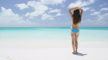 walk behind : Beach vacation travel bikini woman in Caribbean. Lady with slim sexy body standing from behind on tropical white sand beach in Caribbean looking at perfect turquoise ocean. Luxury destination.