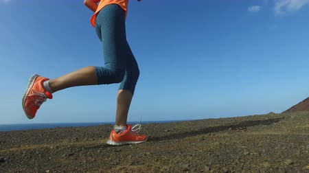 buty sportowe : Running woman outdoors on run. Fast female runner running shoes and legs close up on mountain trail.  Female is in sportswear. Fitness woman exercising in nature on sunny day.  ACTION CAMERA.