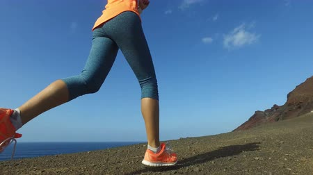 buty sportowe : Trail running sporty young woman runner jogging fast on mountain path against blue sky. Fit female in sportswear exercising in nature on sunny day. ACTION CAMERA TRACKING SHOT.