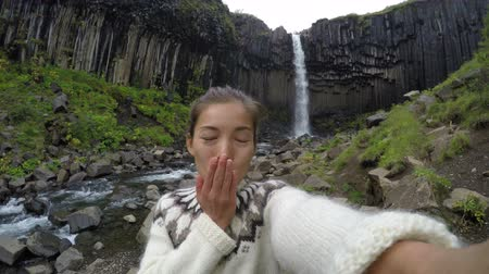 kolumny : Happy woman blowing kiss against majestic Svartifoss waterfall. Female is visiting famous tourist attraction of Iceland. Skaftafell, Vatnajokull National Park, Iceland. ACTION CAMERA.
