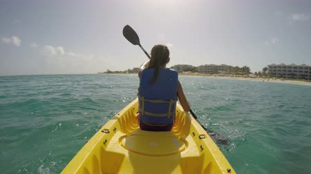 kaland : Young woman kayaking on sea against sky. Female is enjoying her summer vacations at beach. She is wearing life jacket while paddling the kayak. ACTION CAMERA.