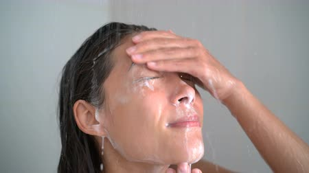 alma : Skincare woman washing face in shower foaming facewash soap on skin. Closeup of female adult cleaning her body showering in hot water at home on in hotel.