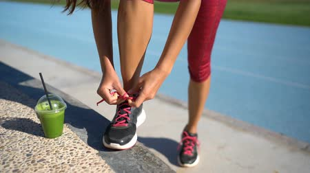 tying : Fitness woman runner tying running shoes next to green smoothie cup on athletic track and field background. Female athlete getting ready for cardio workout run. Feet and legs closeup. Stock Footage
