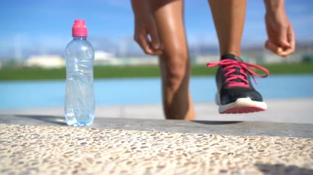 buty sportowe : Sports woman runner getting ready for run tying laces of running shoes next to water bottle on athletic track and field background. Female athlete preparing for fitness cardio workout. Feet closeup.