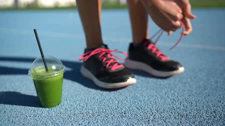 buty sportowe : Female athlete runner getting ready for run race with green smoothie breakfast plastic cup tying running shoes on blue outdoor athletic track. Feet closeup.
