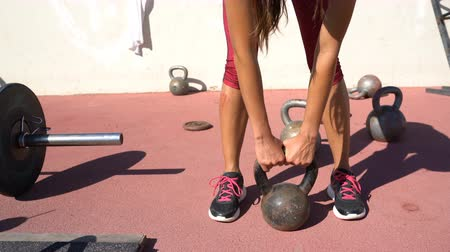 levantamento de pesos : Outdoor crossfit gym - female athlete fitness shoes for weigth lifting getting ready to lift kettlebell weights. Bodybuilding for women concept. Running shoes outside.