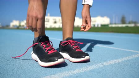 kimerül : Runner woman tying the laces of her running shoes getting ready for race on run track. Female athlete preparing for cardio training .Closeup of feet and hands. Stock mozgókép