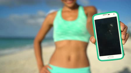 eszköz : Sporty woman showing fitness training app running on phone screen on tropical beach during summer holidays. Unrecognizable runner holding touchscreen for workout or weight loss apps on smartphone. Stock mozgókép