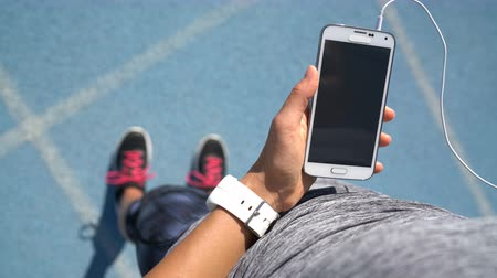 etkinlik : Runner girl holding smartphone using touchscreen for choosing music or texting sms on app before running on track. Female athlete woman feet and leg closeup with smartwatch and hand touching display.