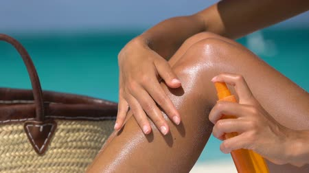 koruma : Sunscreen suntan lotion in spray bottle. Young woman in spraying tanning oil on her leg from bottle. Lady is massaging sunscreen lotion while sunbathing at beach. Female model during summer vacation. Stok Video