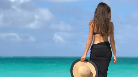 temporadas : Elegant beach woman in black bikini and sarong standing on shore. Sexy female is enjoying wind on beach. Lady is holding sunhat during summer vacation at seaside.