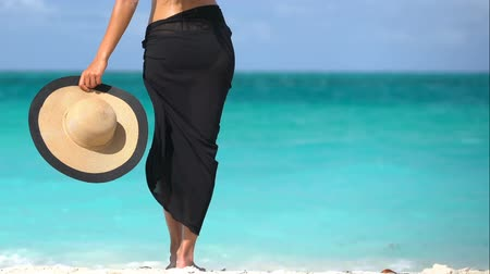 arka görünüm : Lady on beach in black sarong standing on shore looking at ocean. Sexy female is enjoying wind on beach. Woman is holding sunhat during summer vacation by turquoise sea in the Caribbean.