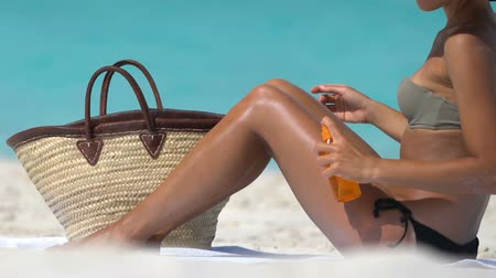 bronzlaşma : Woman applying sunscreen suntan lotion on legs at beach after taking tanning oil spray bottle from beach bag. Young lady is sunbathing at beach. Female in bikini is relaxing during summer vacation. Stok Video