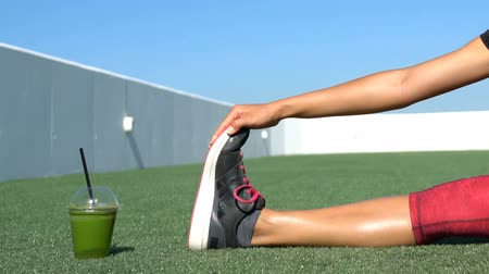 esneme : Sporty young woman exercising by green vegetable juice glass on field. Female is in sportswear. Fit lady stretches legs and hamstrings touching toes while doing stretching exercise on grass.