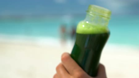 meyve suyu : Hand holding green vegetable smoothie bottle on beach. Closeup of fresh healthy drink held by female on shore. She is enjoying healthy lifestyle drinking kale, spinach and cucumber vege juice