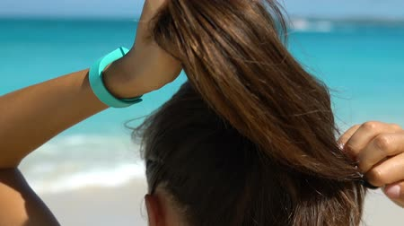 tying : Sporty woman tying ponytail on beach. Runner is preparing herself for running workout on sunny day. Determined female is in sportswear wearing activity tracker watch getting ready. Stock Footage