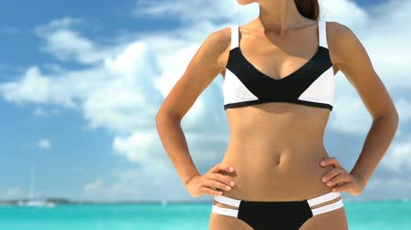 гордый : Sporty young woman in black and white bikini standing on beach wearing sunglasses and sports cap. Confident female is with hands on hip at beach. Fit lady is on summer vacation.