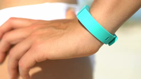 pedometer : Young woman standing with hand on hip at beach. Fit runner is wearing turquoise colored activity fitness tracker watch on sunny day. Female is in white bikini bottom.
