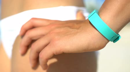 pedometer : Sporty woman standing with hand on hip at beach. Fit young runner is wearing green colored activity fitness tracker watch. Female is in white bikini bottom on sunny day. Stock Footage