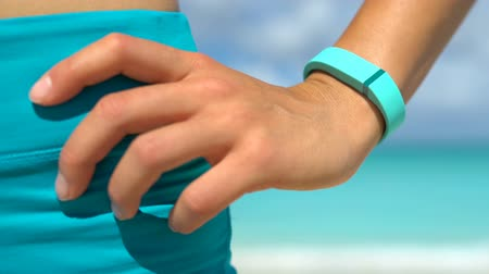 pedometer : Activity tracker on fit young woman wrist standing with hand on hip at beach. Runner is wearing turquoise colored activity fitness tracker watch on sunny day. Female is in sportswear.