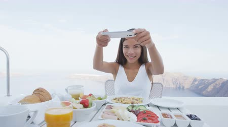 fotografando : Woman taking pictures of breakfast using mobile cell smart phone app. Girl taking photo of food on luxury travel vacation for social media. Beautiful female in resort in Santorini, Greece, Europe. Vídeos