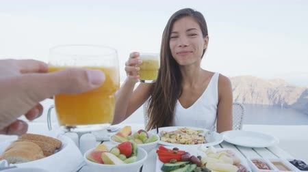 УВР : Couple eating breakfast. Happy tourist woman with man toasting juice glasses on terrace resort. Healthy and delicious food served for breakfast. Lady enjoying healthy drink in Santorini, Greece.
