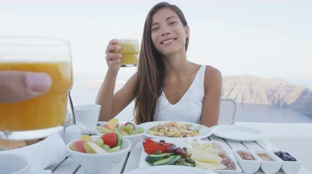 meal : Couple eating breakfast. Smiling tourist woman with man toasting juice glasses on terrace resort. Healthy and delicious food served for breakfast. She is enjoying healthy drink in Santorini.