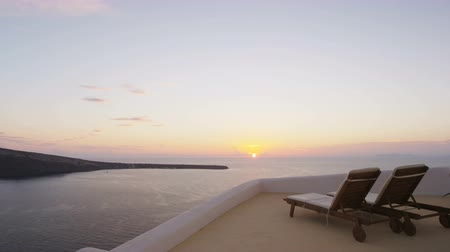 deck chairs : Oia sunset on Santorini famous travel concept. Travel relaxing getaway concept with Deck chairs on the terrace of resort. Scenic view of Aegean Sea and sky. Santorini, Greek Islands, Greece, Europe.