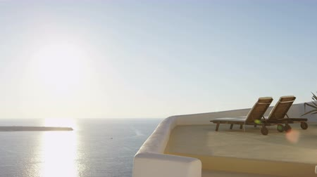 УВР : Travel relaxing getaway concept with Santorini Sunset. Famous Oia sunset with Deck chairs on the terrace of resort. Scenic view of Aegean Sea against sky. Santorini, Greek Islands, Greece, Europe.
