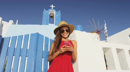 УВР : Tourist on smart phone travel App on Santorini. Young woman using smartphone standing at the entrance of church wearing sunhat and red dress. She is enjoying her summer vacation in Santorini.