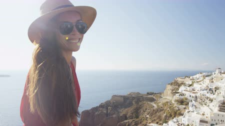 туристическим направлением : Smiling tourist woman enjoying beautiful view of village Oia and sea. Young female is wearing sunglasses and sunhat. She is enjoying her summer vacation in Santorini.