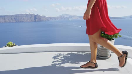 giydirmek : Travel tourist woman walking on in Oia, Santorini. Scenic view of Aegean Sea and caldera from village of Oia. Lady visiting famous island destination in Greece, Europe.