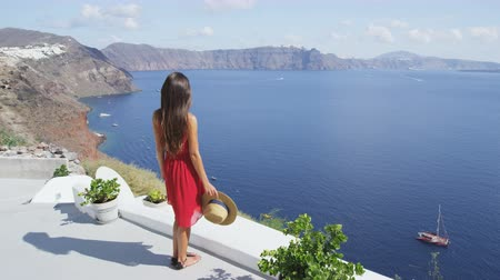 УВР : Santorini tourist walking looking at caldera view and Aegean Sea. Young woman visiting travel destination landmarks wearing red dress on summer vacation Oia, Santorini, Greek Islands, Greece, Europe. Стоковые видеозаписи
