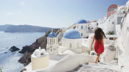 греческий : Elegant woman walking down stairs in Oia Santorini. Female tourist is in red dress on sunny day. She is visiting the famous tourist attraction destination on Europe travel